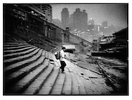 Man descends stairs to board a cross river ferry, this waterfront is now inundated because of Three Gorges of the Yangtze River Dam hundreds of kilometers downstream, Chongqing, China.