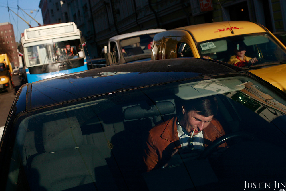 A driver smokes while waiting in traffic in Moscow.