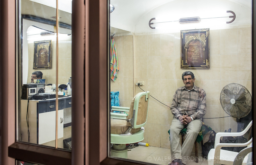 A barber wait for customers in his  shop in the Muslim quarter in the Old City of Jerusalem.