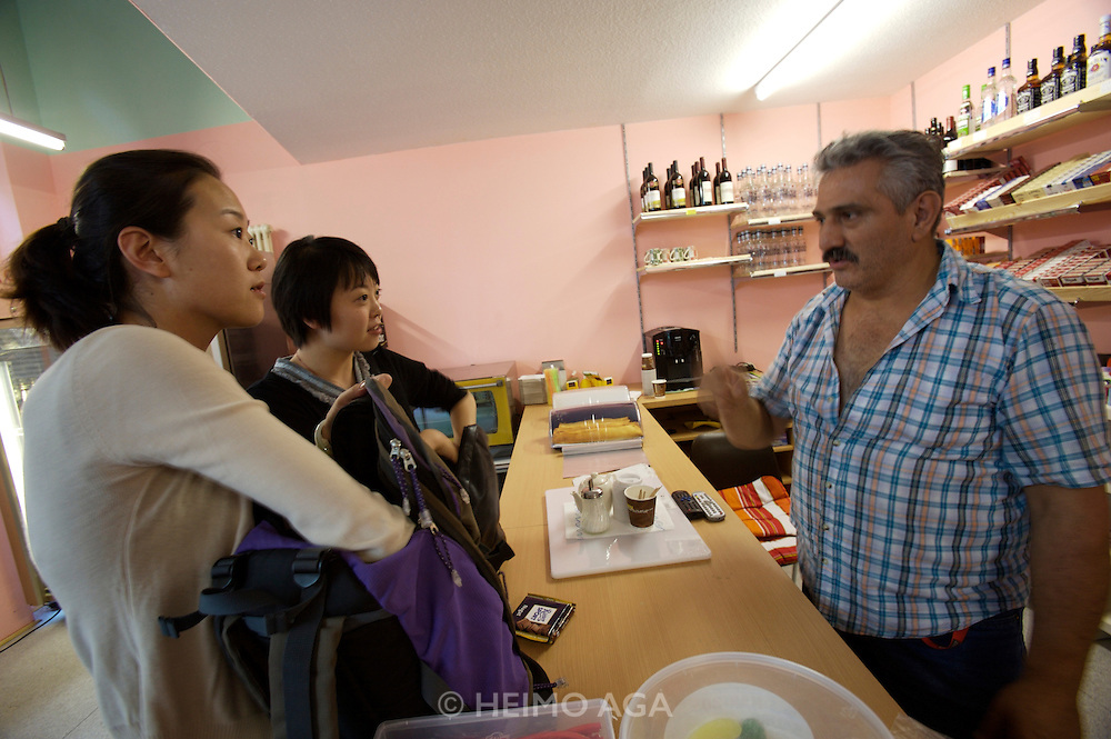 documenta12. Two of Ai Weiwei's 1001 Chinese compatriots are chatting with a Turkish born Kiosk owner while touring the city.