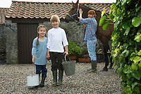 Sister and brother (5-6 7-9) holding buckets mother with horse by stable portrait