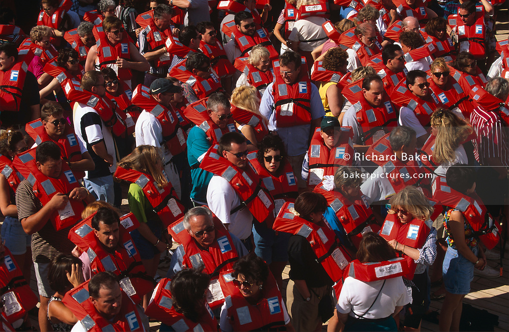 Soon after setting sail from Miami, en-route to Cancun in Mexico, passengers of Carnival Cruise's Fun Ship Ecstasy liner are told to report on the top sun deck for the obligatory safety drill. Told to fetch their life vests from their respective cabins and suites, they have gathered at various muster points around the vessel to hear the crews' instructions about abandoning ship or the precuations needed to enter the water. We look down from a higher deck to see several dozen tourists on red vests, milling around awaiting the signal to return to their previous activities and entertainment. Operators like US-owned Carnival take these drills very seriously. Carnival was a pioneer in the concept of cheaper and shorter cruises. Its ships are known for their Las Vegas decor and entertainment. The cruise line calls its ships The Fun Ships and the MS Ecstasy is a Fantasy class cruise ship featuring two pools, whirlpools, a variety of dining options, nightclubs, a casino, and duty-free shopping. After Hurricane Katrina, she spent six months in New Orleans serving as quarters for refugees and relief workers. She suffered heavy damage in 1998 after the laundry room in the ship's stern caught fire damaging much of her stern and aft section.