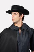 Thoughtful man dressed as Zorro against gray background
