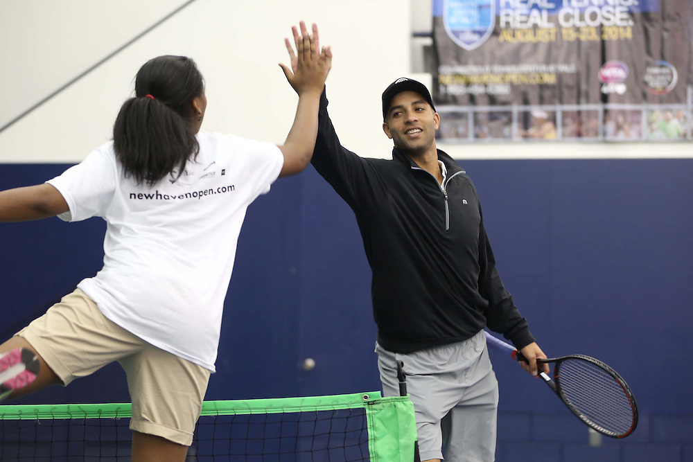 May 15, 2014, New Haven, Connecticut:<br /> Former professional tennis player James Blake high fives a participant during a free tennis lesson and clinic Thursday, May 15, 2014 in advance of the 2014 New Haven Open at the Yale University Tennis Center in New Haven, Connecticut. <br /> (Photo by Billie Weiss/New Haven Open)