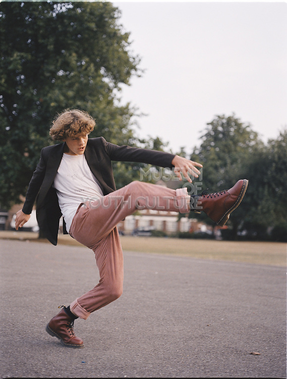 Young man kicking leg up in the air.