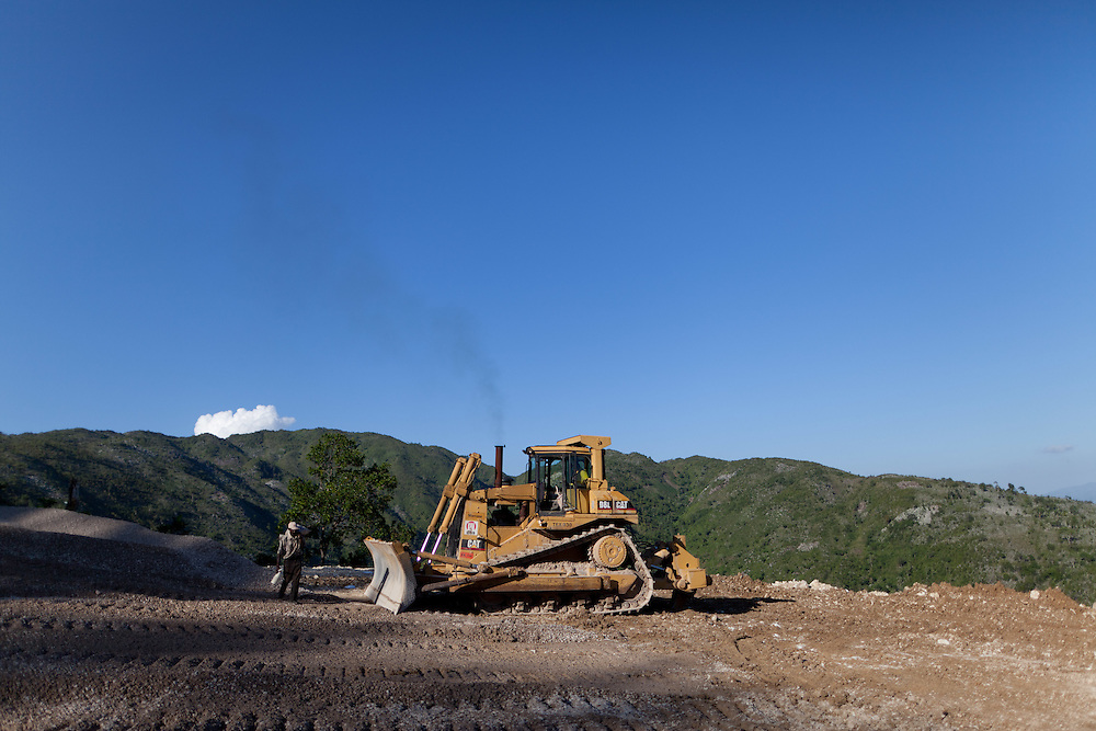 An OAS bulldozer grades a section of road. The Inter-American Development Bank is funding this road project in the south of Haiti, aiming to cut travel time and transportation costs, and to improve living conditions in the southern provinces. This 50-mile stretch of road connects the small cities of Les Cayes and Jeremie and many rural villages in between. A Brazilian company, OAS, is doing the construction. The road is far from complete, but is already transforming commerce and daily life in the area. Travel time has been cut in half; fewer trucks are breaking down, so less food is spoiled; and farmers are planting more crops in anticipation of more dependable farm-to-market transportation.