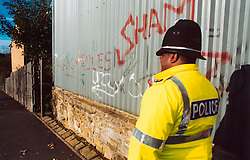 Police officer on the beat walking past wall with graffiti UK