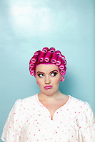 Young woman with curlers on pink hair over colored background