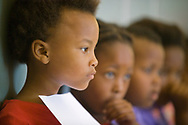 A close up of a girl waiting in line at a Save the Children project, holding her growth and progress record as she waits to get weighed. Cape Town, South Africa.