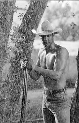 shirtless cowboy working in the rain