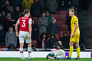 Kieran Tierney (Arsenal) comes over to talk with Mërgim Vojvoda (Liège) with Gabriel Martinelli (Arsenal) still curled up during the Europa League match between Arsenal and Standard Liege at the Emirates Stadium, London, England on 3 October 2019.