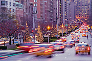 Park Avenue in Manhattan, view at dusk in winter with traffic and Christmas holiday lights on trees, New York City.