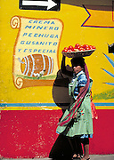 Woman going to market with tomatos on her head  Oaxaca, Mexico