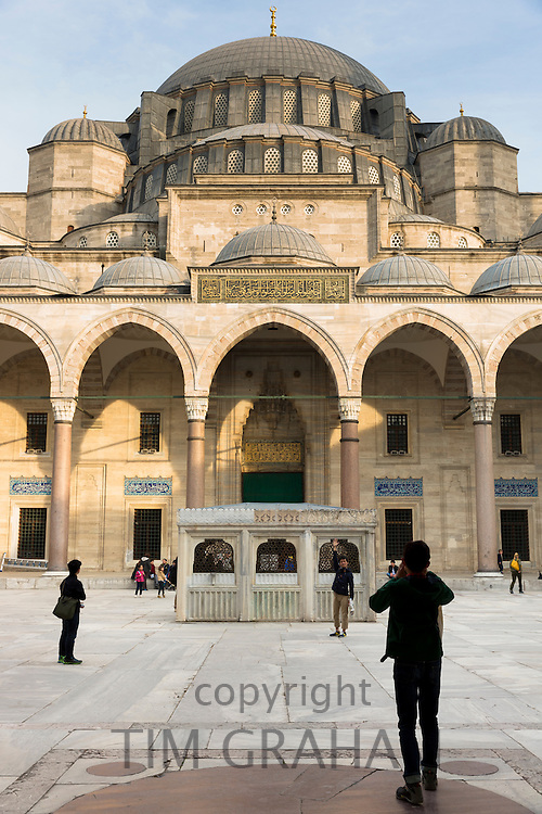 Tourists taking photographs in collonaded courtyard of Suleymaniye Mosque in Istanbul, Republic of Turkey