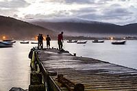 Pescadores em trapiche na Ilha das Campanhas, na Praia da Armação, ao anoitecer. Florianópolis, Santa Catarina, Brasil. / Fishingmen on a pier at Ilha das Campanhas, next to Armacao Beach, at evening. Florianopolis, Santa Catarina, Brazil.