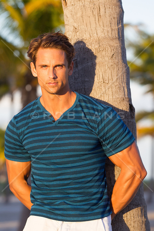 hot All American man against a palm tree at sunset