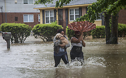 April 25, 2017 - Raleigh, NC, USA - Nautical Jackson, left, and Aniya Ruffin walk through floodwaters with their dog, Chestnut, as water threatens to enter their home on Dacian Road in Raleigh, N.C., on Tuesday, April 25, 2017. (Credit Image: © Travis Long/TNS via ZUMA Wire)