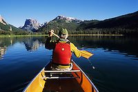 A man canoes across Green River Lake in the  Wind River Mountains, Wyoming (Point Of View).