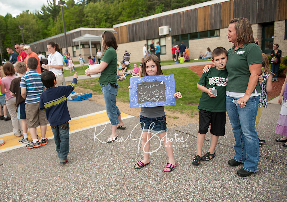 """1Pipa Boyle holds a """"thank you"""" card for Laconia Police and Fire signed by Mrs. Mull's 2nd grade students from Woodland Heights Elementary School during their Read In / Cookout on Friday afternoon.  (Karen Bobotas/for the Laconia Daily Sun)"""