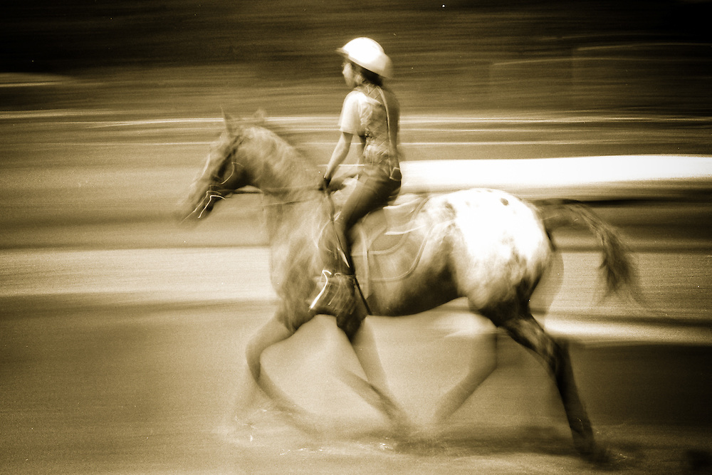 Black and white image of a horse and rider, blurred to create a sense of motion
