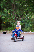 Young brother and sister riding on a tricycle and laughing in a garden setting.