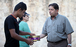 August 27, 2017 - Jerusalem, Jerusalem, Palestinian Territory - A Palestinian man distributes sweets to people as part of celebrations marking Israel's removal of all security measures it had installed at the compound known to Muslims as Noble Sanctuary and to Jews as Temple Mount, in Jerusalem's Old City July 27, 2017  (Credit Image: © Amir Abed Rabbo/APA Images via ZUMA Wire)