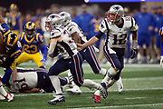 New England Patriots running back Rex Burkhead (34) takes a handoff from New England Patriots quarterback Tom Brady (12) as he runs for a fourth quarter gain of 26 yards and a first down at the Los Angeles Rams 33 yard line during the NFL Super Bowl 53 football game on Sunday, Feb. 3, 2019, in Atlanta. The Patriots defeated the Rams 13-3. (©Paul Anthony Spinelli)