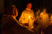DENVER, CO - APRIL 19: Father Roger Lascelle, left, lights a candle during the start of the Easter Vigil Mass at the Cathedral Basilica of the Immaculate Conception on April 19, 2014, in Denver, Colorado. (Photo by Daniel Petty/Denver Catholic Register)