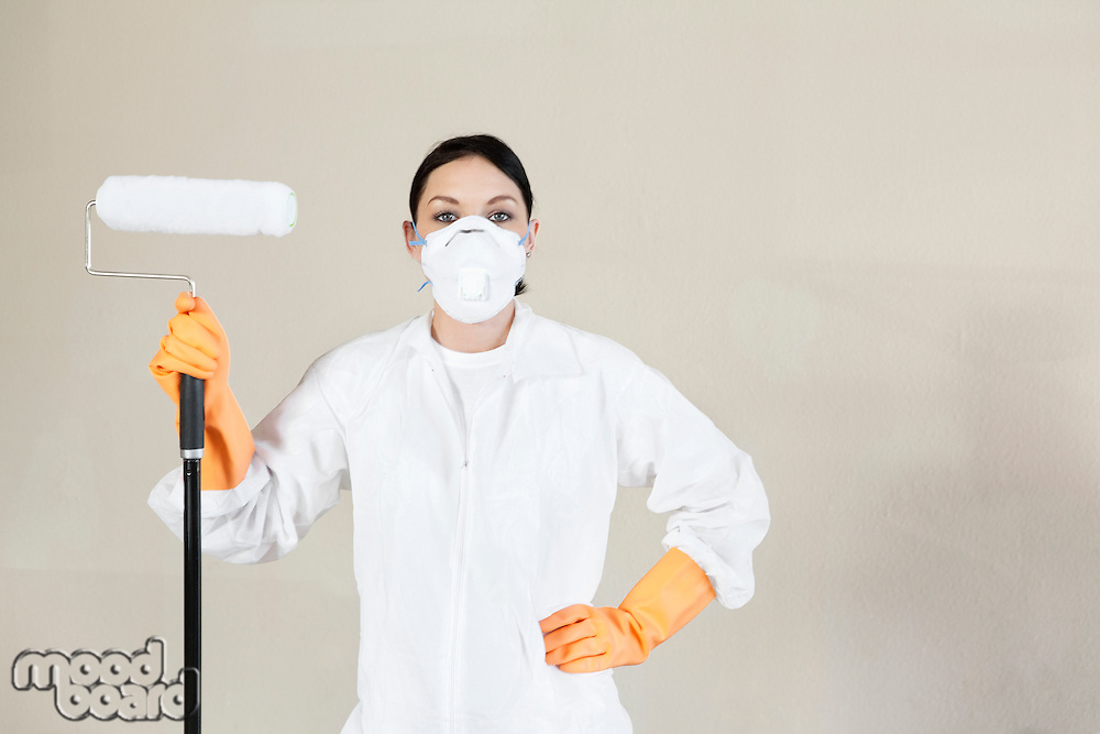 Portrait of a female worker in protective workwear holding paint roller with hand on hip