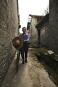 Old man with bycicle walks through the ancient Cha Tang Village, at Guangzhou periphery. Guangdong, China.