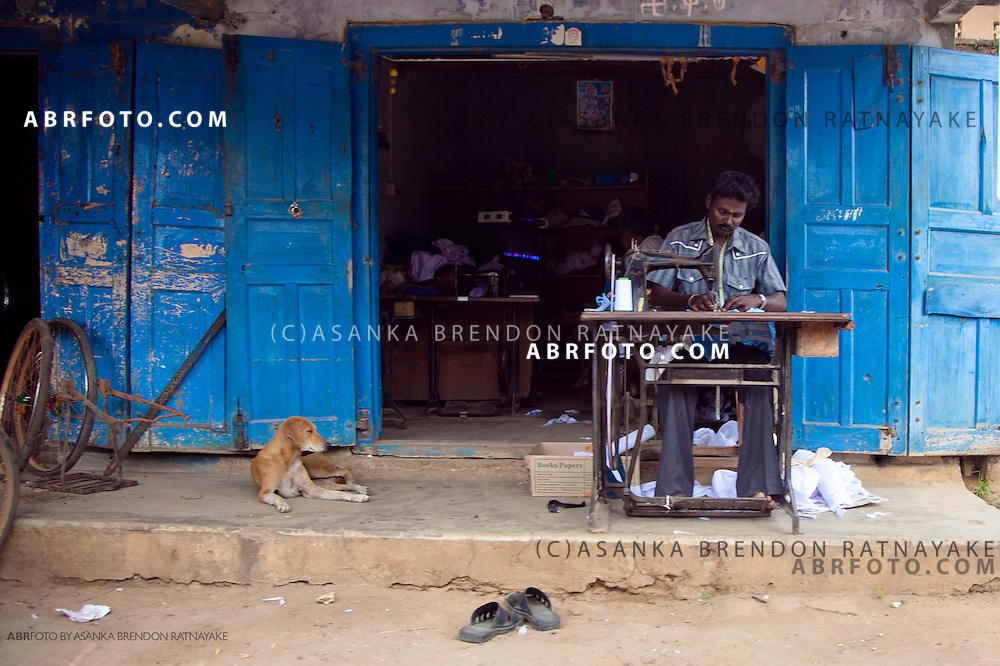 Tailor operating a sewing machine outside.
