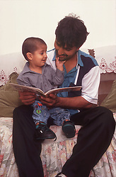 Father reading to young son,