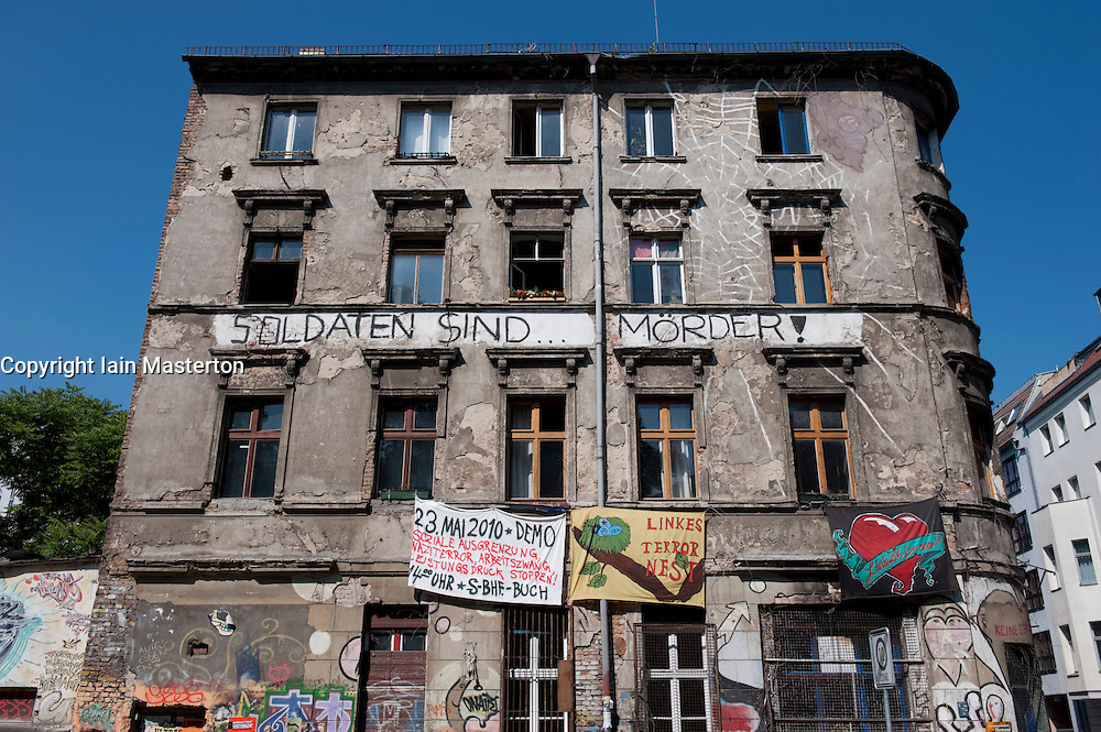 Old apartment building with squatters living inside and protest banners hanging on wall in Berlin Germany