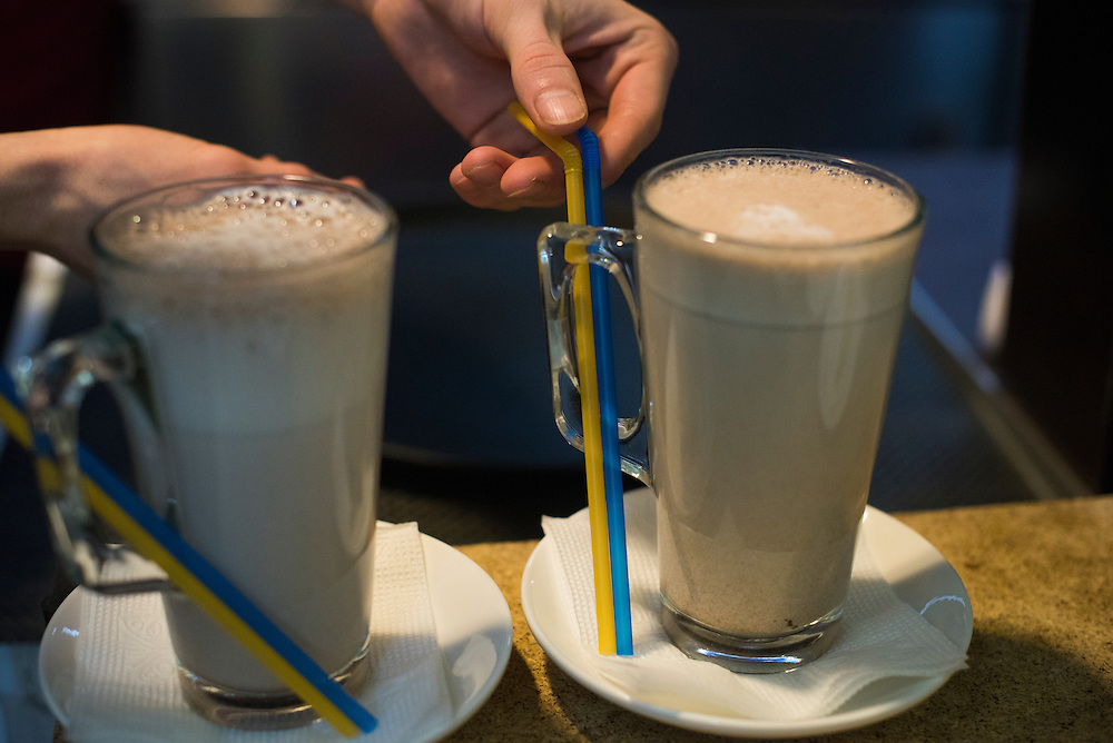 Ilya Galchuk, a student who prepares coffee, tea and other beverages for customers at Veterano Pizza, places patriotically-colored straws in glasses of chocolate milk, on January 23, 2016 in Kiev, Ukraine. (Pete Kiehart for The New York Times)