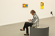 A woman checks her phone outside the booth of Hauser & Wirth, The paintings on the wall are by Mary Heilman.