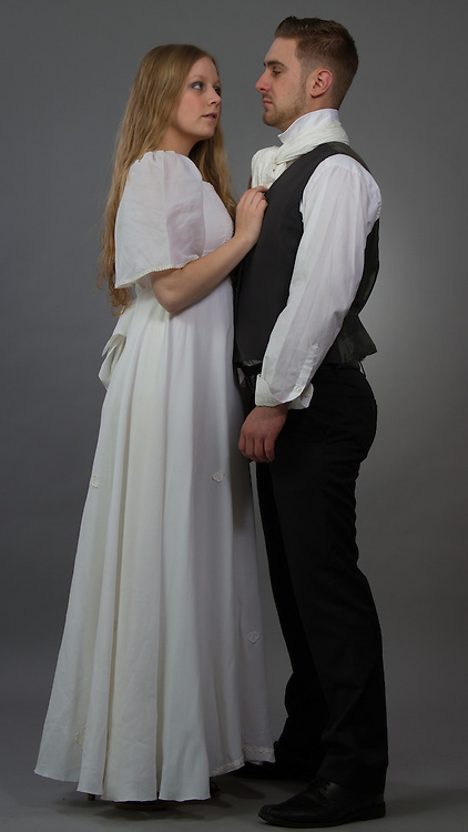 A couple posing in regency outfits.