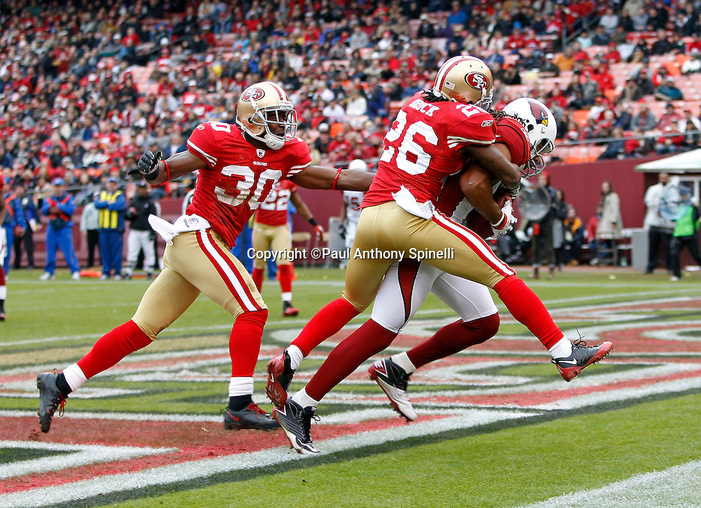 Arizona Cardinals wide receiver Larry Fitzgerald (11) catches a second quarter touchdown pass that cuts the San Francisco 49ers lead to 10-7 while covered by San Francisco 49ers safety Reggie Smith (30) and San Francisco 49ers cornerback Tramaine Brock (26) during the NFL week 17 football game on Sunday, January 2, 2011 in San Francisco, California. The 49ers won the game 38-7. (©Paul Anthony Spinelli)