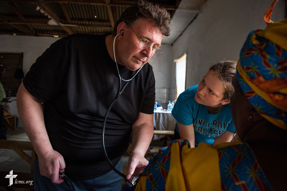 The Rev. Michael Awe, team leader and pastor at Hope Lutheran Church, South Sioux City, Neb., works with Hayden Rensner, a student at Concordia University, Nebraska, on the third day of the LCMS Mercy Medical Team on Wednesday, May 9, 2018, in the Yardu village outside Koidu, Sierra Leone, West Africa. LCMS Communications/Erik M. Lunsford