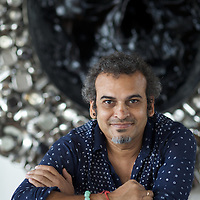 "Subodh Gupta, contemporary artist in his recently completed studio in Gurgaon, a satellite town of Delhi...Gupta's most celebrated sculptures are constructed from common domestic items including the steel pots and pans that are a feature every Indian home. Of the kitchen-ware that forms the basis of his work, Gupta says,..""The poor, the middle class and the rich use it at home. In this country, how many people have the utensils but they starve because there is no food?""..Gupta was brought up, one of six children, to a railway-worker father in a north Indian village. ..Gupta's work fetches such huge sums of money. Two versions of his Mind Shut Down, modeled on the human skull and constructed entirely of steel kitchen utensils recently sold for EUR1 million each...Photo: Tom Pietrasik.Gurgaon, Haryana. India. .July 23rd 2009"