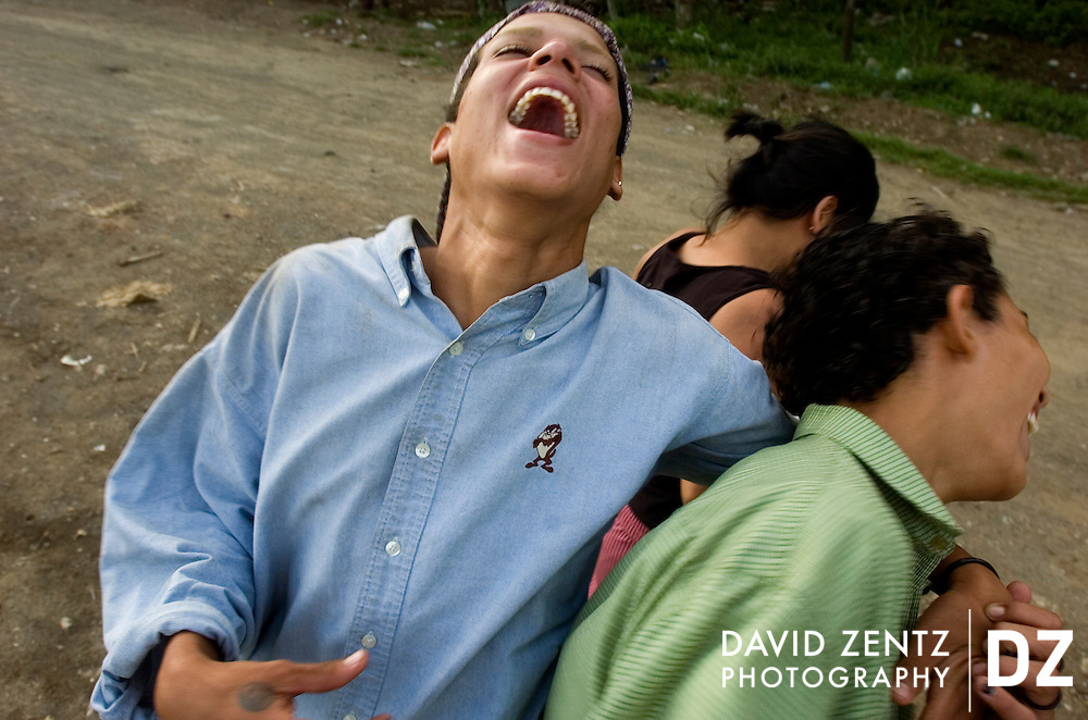 Rene Ruiz, 16, gets a kick out of having his picture taken with his friends while the three head down a road along the outer edge of Jinotepe, Nicaragua on October 3, 2004.