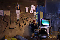 A rebel sits in the courthouse in Benghazi that houses the temporary rebel headquarters wathing the latest news of fighting on al-Jazeera. Local artists transformed ithe courthouse walls into colourful anti-regime collages