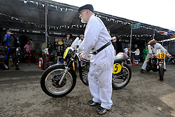 © Licensed to London News Pictures. 17/09/2011. GOODWOOD, UK. Mechanics return motorcycles to the garages. The Goodwood Revival at Goodwood in West Sussex today (17 September 2011). The revival is the world's largest historic motor race meeting, which relieves the 'glorious' days of the race circuit. Competitors and enthusiasts all dress in period fashion to enhance the experience. Photo credit : Stephen Simpson/LNP