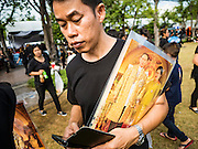 22 OCTOBER 2016 - BANGKOK, THAILAND:  A mourner carries a portrait of Bhumibol Adulyadej, the King of Thailand, across Sanam Luang in Bangkok. Sanam Luang, the Royal Ceremonial Ground, was packed Saturday with more than 100,000 people mourning the Monarch's death. The King died Oct. 13, 2016. He was 88. His death came after a period of failing health. Bhumibol Adulyadej was born in Cambridge, MA, on 5 December 1927. He was the ninth monarch of Thailand from the Chakri Dynasty and is also known as Rama IX. He became King on June 9, 1946 and served as King of Thailand for 70 years, 126 days. He was, at the time of his death, the world's longest-serving head of state and the longest-reigning monarch in Thai history.      PHOTO BY JACK KURTZ