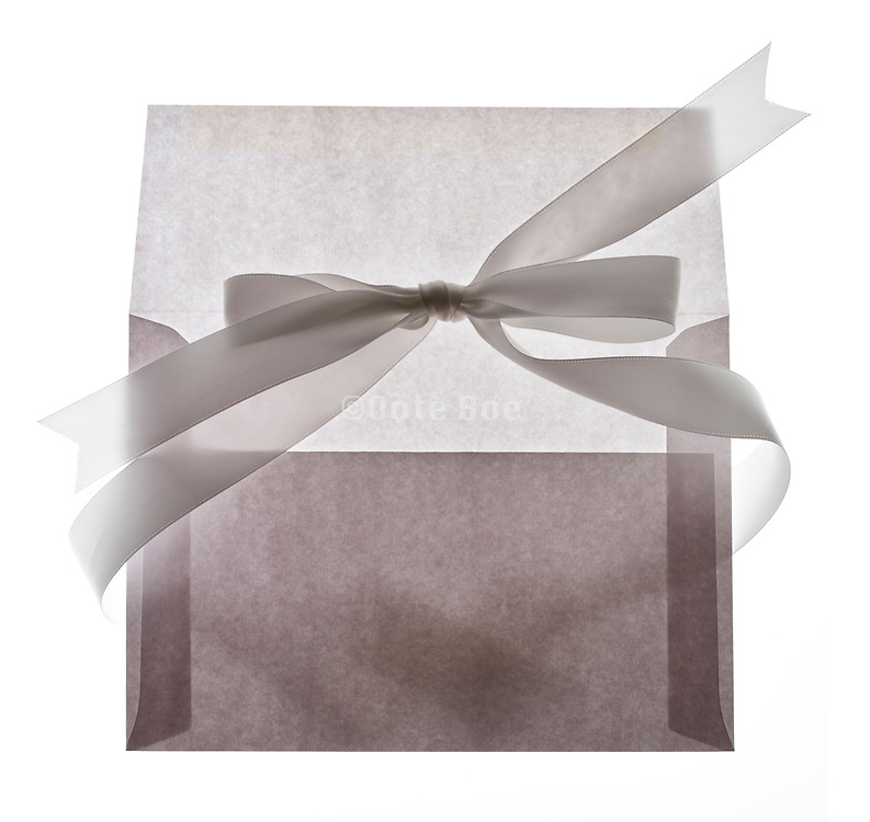 white bow ribbon around a envelope