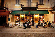 People enjoying an enoteca (winebar) at night in Orta San Giulio, Piedmont, Italy. For editorial use only.