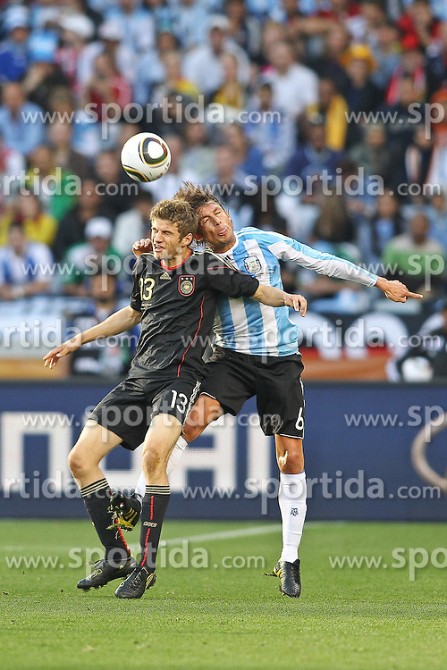 03.07.2010, CAPE TOWN, SOUTH AFRICA, im Bild .Thomas Mueller of Germany and Gabriel Heinze of Argentina challenge for the ball during the Quarter Final, Match 59 of the 2010 FIFA World Cup, Argentina vs Germany held at the Cape Town Stadium.Foto ©  nph /  Kokenge