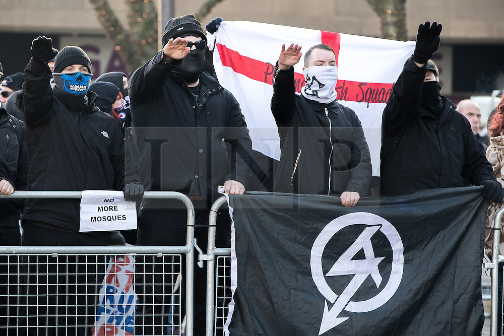 "© Licensed to London News Pictures . 26/11/2016 . Bolton , UK . Those opposed to mosques , pictured giving Nazi salutes at the demonstration behind a flag of the far right group , National Action . Approximately 100 people attend a demonstration against the construction of mosques in Bolton , under the banner "" No More Mosques "" , organised by a coalition of far-right organisations and approximately 150 anti fascists opposing the demonstration , in Victoria Square in Bolton Town Centre . Photo credit : Joel Goodman/LNP"