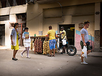Transaction at the vegetable cart bicycle as a nurse, doctor and tourist pass by in Havana.
