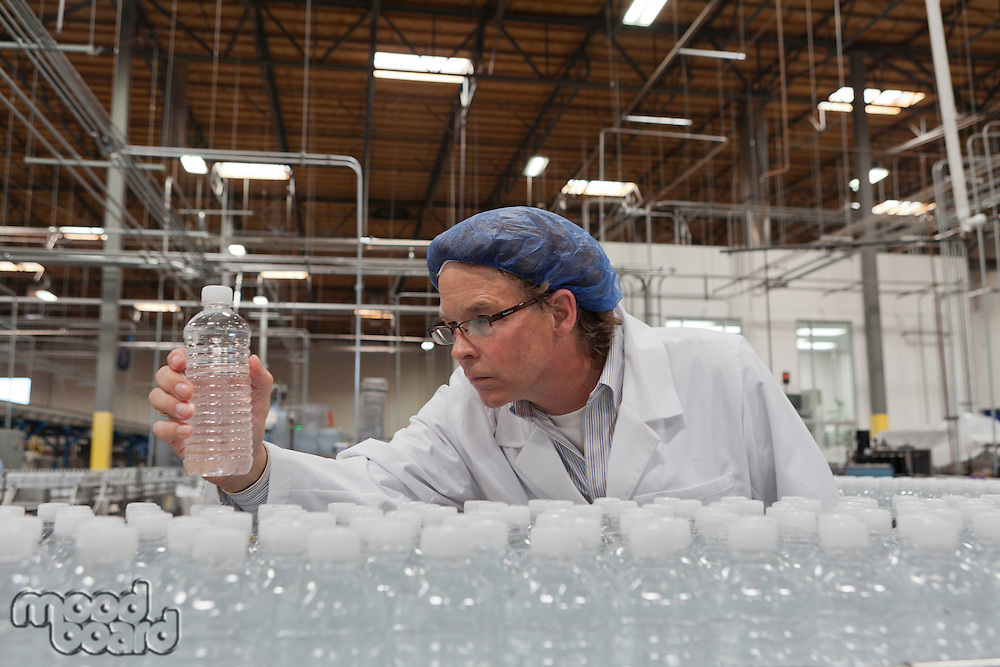 Quality control worker checking bottled water at bottling plant
