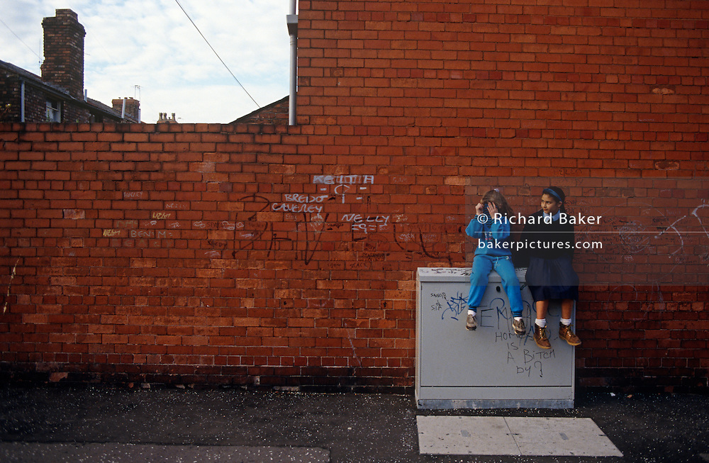 Two young 'Scouse' girls sit on a telephone junction box and against a brick wall on which there is graffiti and childish scribbles. They are near a back alleyway between poor terraced housing in Liverpool, England. The older, taller girl is of Asian-descent and the younger is White British who hides her face with her top. Both are facing other activity in this inner-city street where there are 'back to back' houses in a poor area, South of the city centre and home to deprived families. Few of these back-to-backs exist after being cleared to allow construction of high-rise tower-blocks and flats.